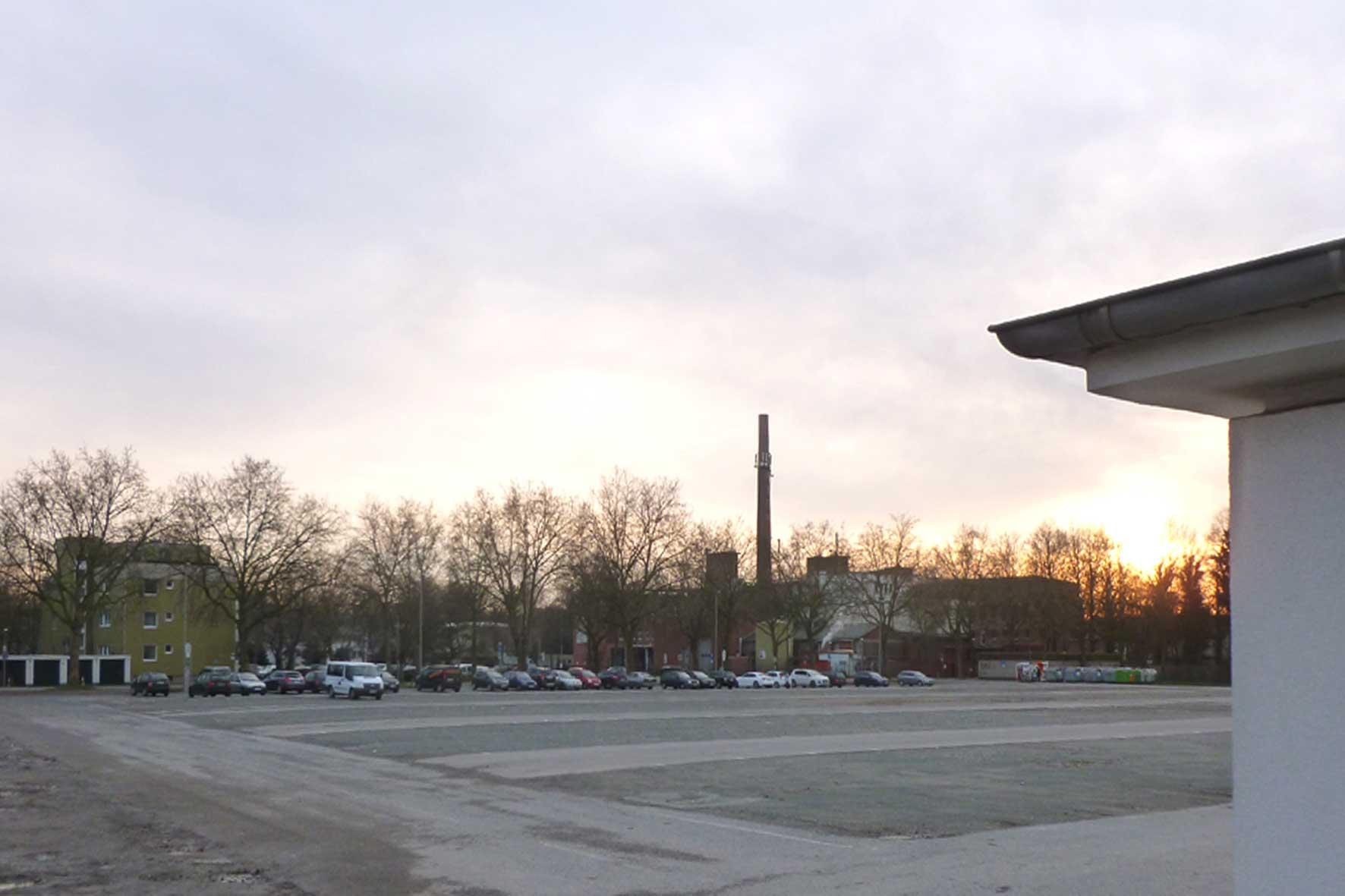 Das Foto zeigt den Marktplatz in Gütersloh bei Sonnenuntergang mit viel freier Fläche.