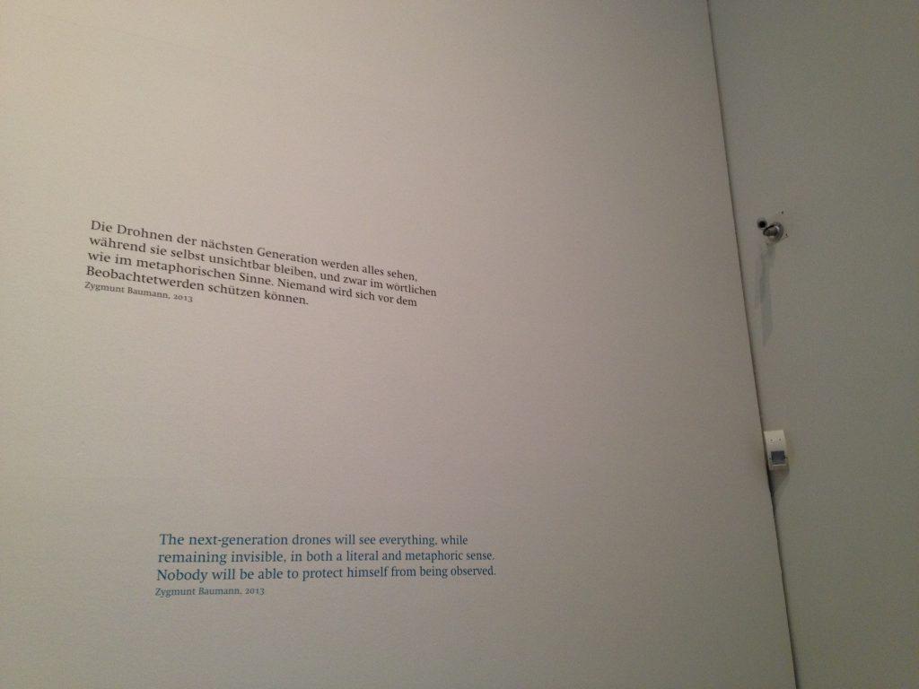 Das Foto zeigt einen Text zu Drohnen und eine Überwachungskamera.