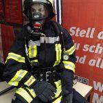 Das Foto zeigt einen Feuerwehrmann in Schutzanzug und Helm.