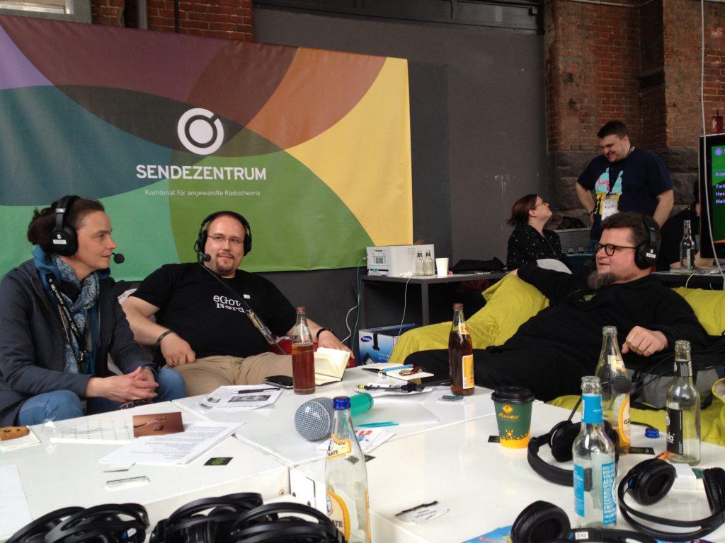 Das Foto zeigt drei Menschen mit Kopfhörern bei der Aufnahme.