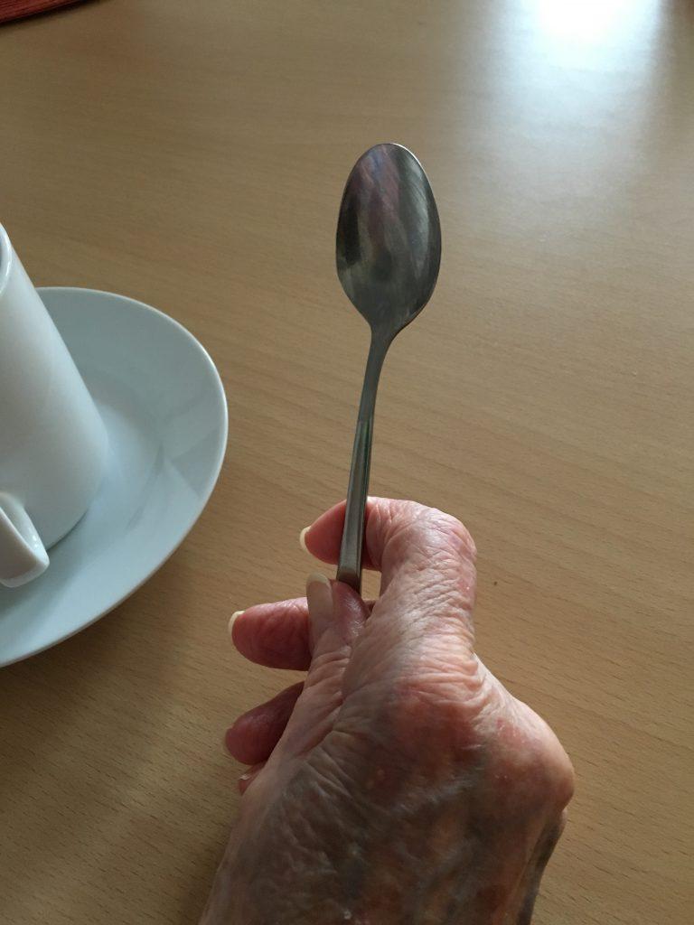 Das Foto zeigt eine alte Hand mit einem Löffel in der Hand, im Hintergrund eine Kaffeetasse.