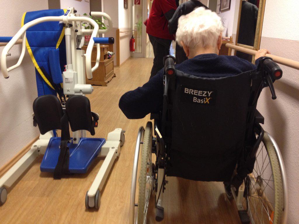 Das Foto zeigt eine ältere Dame in einem Rollstuhl aber nur von hinten.