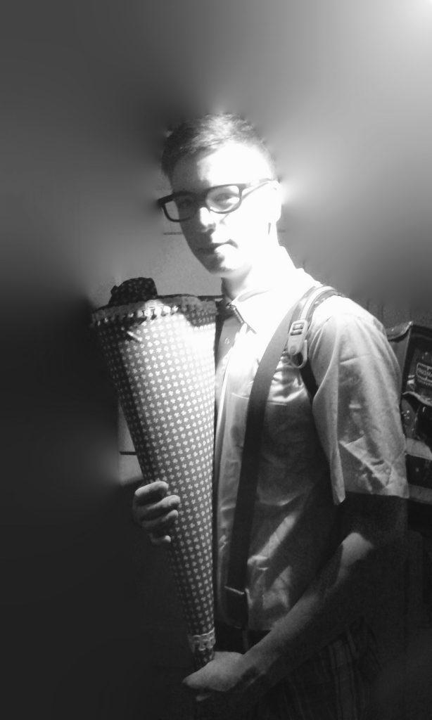 Das Foto zeigt einen jungen Mann mit Schultüte.