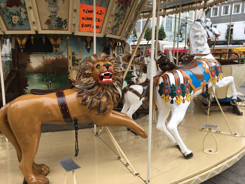 Das Foto zeigt ein Karussell mit Löwe und Pferd.