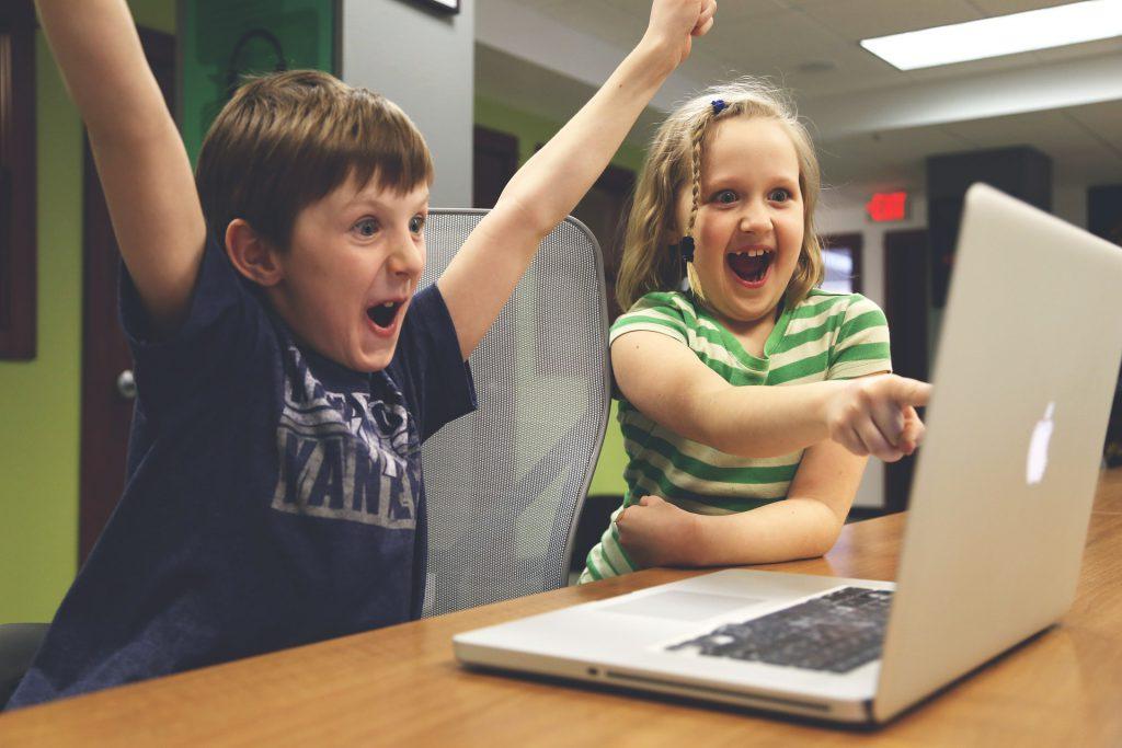 Das Foto zeigt zwei Kinder vor dem Rechner