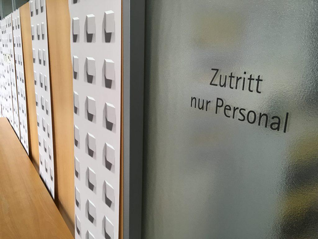 Das Foto zeigt eine Kunstinstallation mit Tapete und Legomuster vor Bürotür.