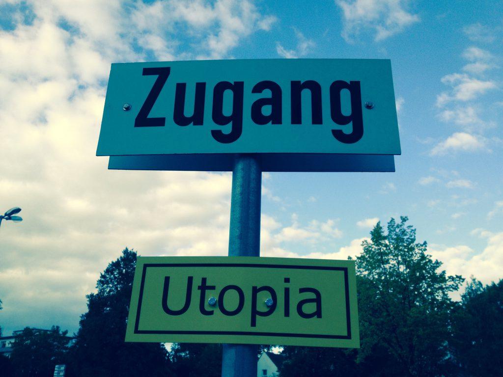 Das Foto zeigt zwei Schilder mit Zugang und Utopia.