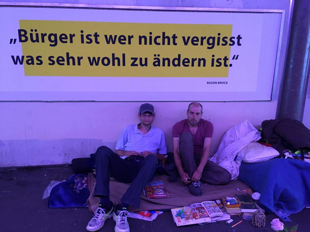 Das Foto zeigt zwei Obdachlose unter einer Brücke.