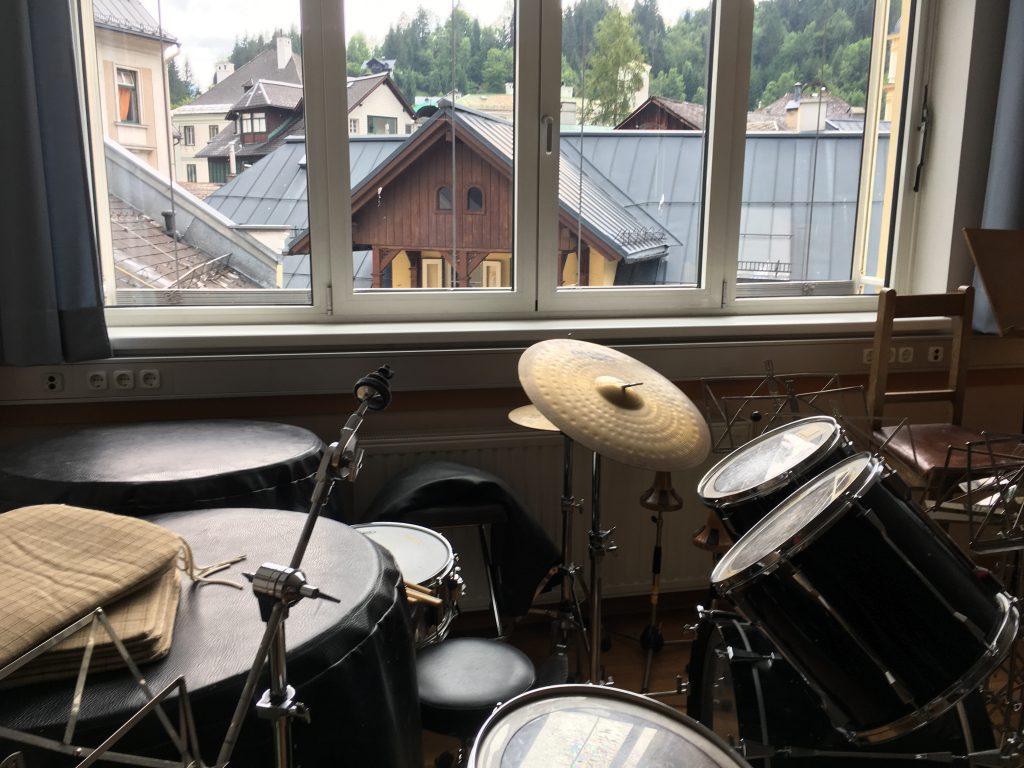 Das Foto zeigt ein Schlagzeug mit einem Blick aus dem Fenster auf Dächer und Berge.